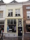 foto van Huis met schilddak en witgepleisterde lijstgevel, bovenlicht met paard en Lodewijk XVI ornament, deur uit dezelfde tijd