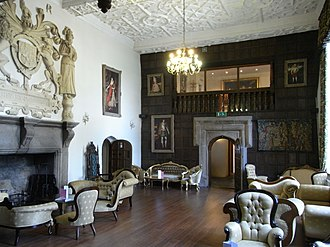 Boringdon Hall - The Great Hall, Boringdon, looking eastwards. The stone doorway now in the centre of what would originally have been the screens passage was moved from the SW room of the house. The woodwork, floor and decorative plaster ceiling are all modern; the pictures are photographic reproductions. The Great Hall however retains its original grand proportions and is lit by two double-height windows on the south side