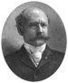 "Head of a balding white man with a bushy mustache wearing pince-nez glasses and a dark suit over a light-colored shirt and tie. The portrait is framed by laurel wreaths on the bottom and the words ""HON. HENRY H. BINGHAM"" are below."