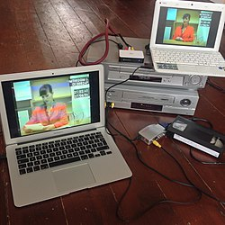 A laptop with the game footage sits atop two VHS players. Wires connect them to another laptop nearby, with a VHS cartridge to the right.