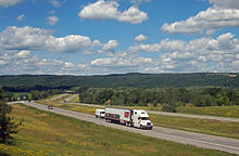 "A divided expressway curves from the right of the image through a mostly wooded landscape towards a ridgeline at the rear below a blue sky filled with little white fluffy clouds. Along the roadway closest to the camera is a large white truck with ""Perry's Ice Cream"" along the side and pictures of scoops of ice cream in various colors and flavors"