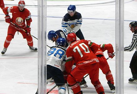 Skaters from the Finnish and Belorussian men's ice hockey teams shortly after a face-off during the 2016 IIHF World Championship. The IIHF is an annual national team tournament. IIHF16WC - Game FIN v BLR.jpg