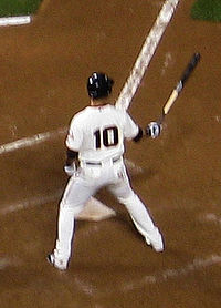 A baseball player with a black number 10 on the back of his uniform prepares to hit