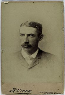 A sepia-toned image of a mustachioed man with thick, parted hair