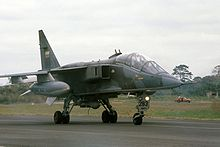 Jet aircraft in mostly green camouflage scheme taxiing.