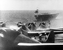 Photograph showing four aircraft lined up with several men working nearby. The sea and a complete ship are visible in the distance, along with the horizon and some sky.
