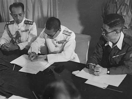 A Japanese officer signs the surrender of Penang aboard HMS Nelson on 2 September 1945.