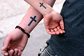 Religious perspectives on tattooing - A Christian couple with matching cross symbol tattoos to associate with their faith