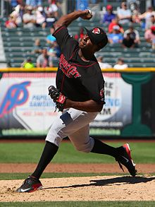 "A man wearing a black baseball jersey with ""Music City"" written across the chest, gray pants, black socks, and a black cap in the midst of pitching a baseball from the mound"