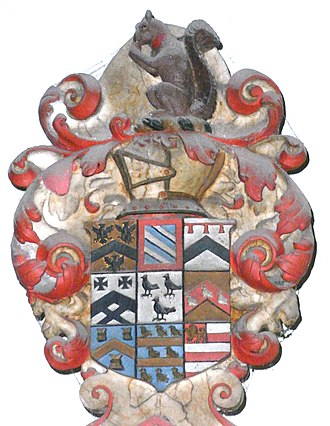 John Bluett - Escutcheon above monument to Sir John Bluett (d.1634) in Holcombe Rogus Church, showing 8 quarterings with the Bluett crest above, a squirrell eating a nut