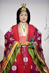 A young woman with her hair down wearing several layered pink and green Heian-period kimono