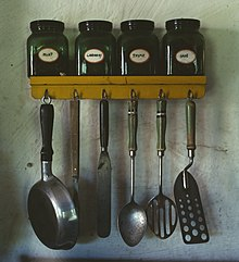 Various kitchen utensils.  At top: a spice rack with jars of mint, caraway, thyme, and sage.  Lower: hanging from hooks; a small pan, a meat fork, an icing spatula, a whole spoon, a slotted spoon, and a perforated spatula.