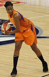 Young woman wearing orange basketball uniform leaning to her right carrying the ball
