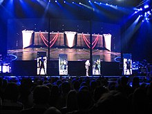 A stage with four rectangular screens which display a black geometric patterned screen approaching. In front of the screen stands Madonna and her three dancers, clad in a robotic outfit