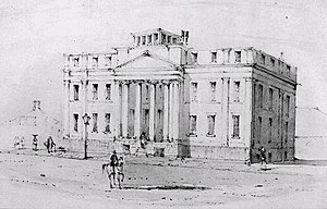 Black and white drawing of a large three-storey building fronted by a four-column portico. A man on a light-coloured horse is riding down the wide empty street in front of the building