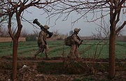 Two marines walking along the edge of a field, one of them carrying a Javelin missile tube