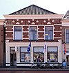 foto van Huis met verminkte bakstenen gevel zonder top met zandstenen banden, blokjes en beeldhouwwerk en gewijzigde onderpui