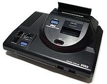 Photo d'une Mega Drive surmontée d'un boitier permettant de lire des cartouches de jeux Master System