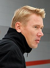 Head and shoulders of a man in his late thirties with blonde hair and grey eyes, facing to the right. He is wearing a black polo neck sweater.