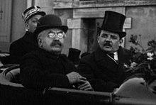 Twee mannen met jassen en hoeden die achter in een paardenkoets zitten;  de persoon aan de linkerkant heeft grijswit haar, zwarte wenkbrauwen, een bril en een grijze snor;  die rechts heeft zwart haar en snor, een wit overhemd en een donkere stropdas