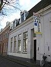 foto van Winkelpand onder afgeplat schilddak met gepleisterde lijstgevel 19e eeuw. Voor een oudere kern; schuiframen met roedenverdeling, gestucte pilasters en blokken boven de vensters