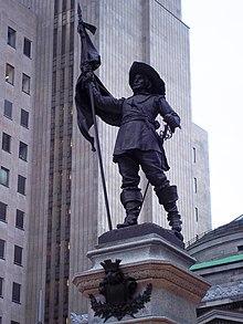 Statue de Maisonneuve portant fièrement un drapeau de la main droite et une épée à la main gauche. Il porte un large chapeau au bord relevé, une tunique, des pantalons et de hautes bottes aux bords repliés.