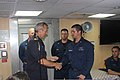 Netherlands navy Commodore Ben Bekkering, foreground left, commander of NATO Task Force 508, presents a challenge coin to U.S. Navy Cryptologic Technician 3rd Class Chadwick Anderson, foreground right, during 120809-N-XQ232-1884.jpg