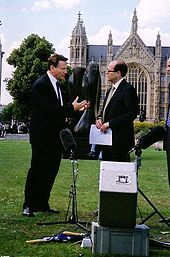 Two men in suits, stood on a grassy field in front of a Gothic style building. There is a tree on the left side, and microphone and recording equipment in the foreground on the floor.