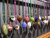 Colourful four-hole English pendant ocarinas hanging from a rail by elaborately-knotted 2- and 3-colour lanyards. Three are shaped like squat owls; several have low-relief or painted patterns.