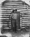 Phil Bartlett standing in front of cabin he shared with Bartie Osborne during the Gold Rush, Nome, Alaska, probably 1900 (AL+CA 8128).jpg