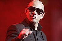 Picture of a man in a suit, wearing sunglasses and holding a microphone in his hands against a red backdrop.