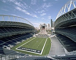 The interior of a stadium from the upper tier behind the south end zone during the day. The end zones and seating sections are colored blue. At the north end is a smaller seating area at the base of a tower. Several high-rise office buildings are in the distance.