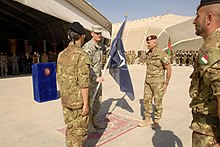 An older general hands a blue and white flag from a soldier on the left to one on the right. Other soldiers stand in a line around these three, watching this ceremony.