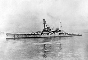 A large gray warship sits motionless in harbor. Several other ships are faintly visible in the distance.