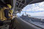 Sailor ties a messenger line to a shot line on a fueling sponson of USS Dwight D. Eisenhower (26159445962).jpg