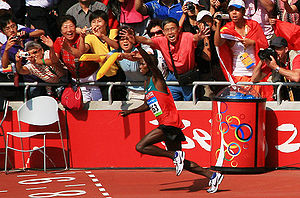 Marathon - Samuel Wanjiru raises his hand in acknowledgment of the crowd as he runs to a gold medal in the 2008 Olympic marathon