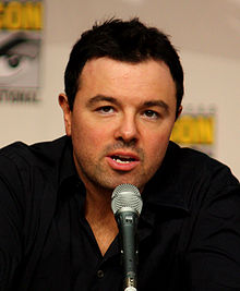 A Caucasian male with black hair and stubble, along with a black shirt. His hand is placed under his chin and a microphone is in front of him. A vague simple is marked behind him.