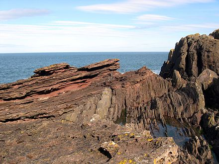 An eroded outcrop at Siccar Point showing sloping red sandstone above vertical greywacke was sketched by Sir James Hall in 1788. Siccar Point red capstone closeup.jpg