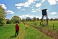 Spaziergängerin mit Hund neben Hochsitz Deutschland 09.png