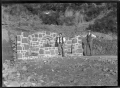 Stone construction which includes a fountain with water falling into a pool or trough; a rocky area in front, and sloping hill above. Two unidentified men are standing in front ATLIB 327451.png
