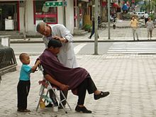 barber cuts hair on the streets of Harbin, China.