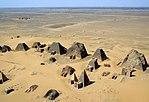 An aerial view of a dozen pyramids in relatively bad shape in the foreground, and a deserted view in the background.