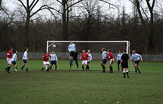 Sunday league football - A Sunday league match in Manchester in 2007.  Such matches often take place in public parks with boggy hilly pitches without spectator accommodation or other facilities