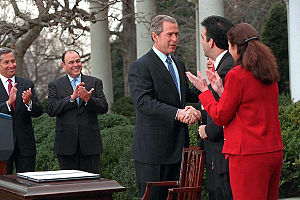 President George W. Bush signs papers with Lat...