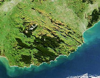 The Catlins - Forested areas show dark green in this satellite picture of the Catlins. The area's parallel strike ridges - part of the Southland Syncline - can clearly be seen running from north-west to south-east in the northern part of this image.