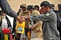 The assistant district chief of police for Nawbahar district, right, helps distribute bottles of cooking oil with an Afghan National Police (ANP) officer before distributing them to families in Pinzo village 120205-N-UD522-121.jpg