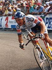 A man riding a bike in a cycling jersey.