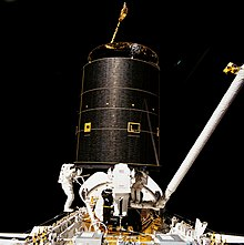Three astronauts capture the Intelsat VI F-3 satellite during STS-49