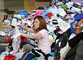 "Tomoko Bristow, from Misawa, Japan, helps sort and organize clothing donated to Japan by listeners of the ""Ron and Don"" radio show at Naval Air Facility Misawa, Japan, June 23, 2011 110623-N-TW583-062.jpg"