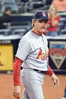 Man walking towards the left turning his head to face the camera.  He is wearing a gray St. Louis Cardinals uniform with red sleeves and a dark St. Louis Cardinals hat.